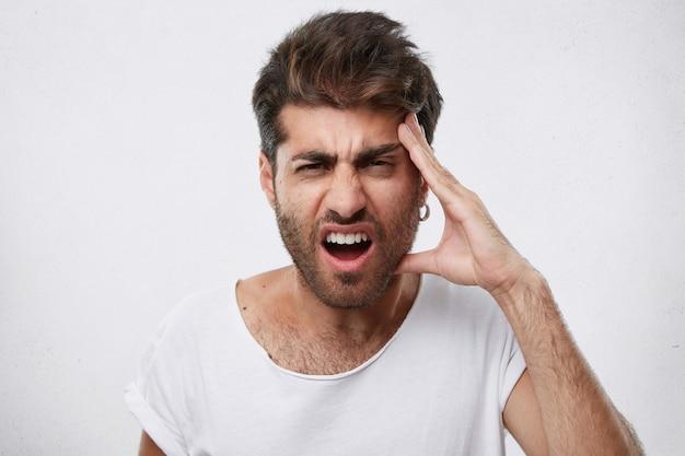 Portret van depressieve man met dikke baard die zijn hand op het hoofd houdt met hoofdpijn die verdrietig is