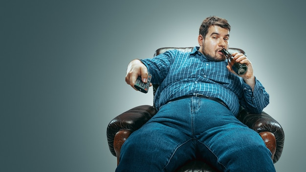 Portret van dikke blanke man met jeans en whirt zittend in een bruine fauteuil geïsoleerd op een grijze achtergrond met kleurovergang. tv kijken, bier drinken en van zender wisselen, lachen. overgewicht, zorgeloos.