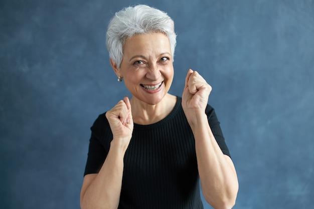 Portret van dolblij gelukkig vrouwelijke gepensioneerde m / v met stijlvol kapsel camera kijken met vrolijke brede glimlach, gebalde vuisten, opwinding uiten.