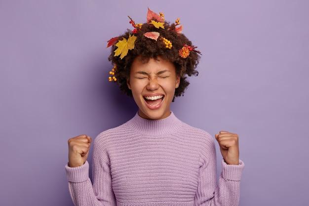 Portret van dolblij jonge afro-vrouw balde vuisten met succes, voelt zich opgewonden, heeft creatieve kapsel versierd met herfstbladeren, draagt een warme trui, geïsoleerd op paarse achtergrond.