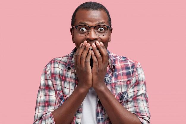 Portret van dolblij verbaasd afro-amerikaans mannetje bedekt de mond, is dolblij als hij een voorstel voor een goede baan ontvangt, geïsoleerd over roze