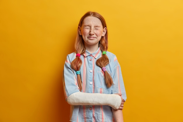 Portret van dolgelukkig meisje kan niet stoppen met lachen, poses met gesloten ogen heeft rood haar gekamd in paardenstaarten terloops gekleed voelt zich erg blij heeft gebroken arm. kinderen, emoties, natuurlijke schoonheid