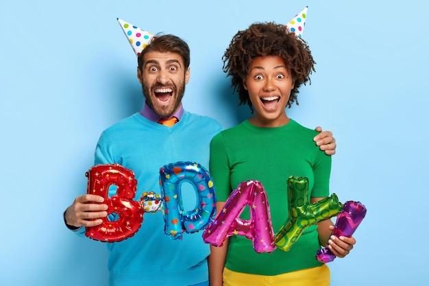 Portret van dolgelukkig paar omhelzen en houden briefvormige ballonnen vast