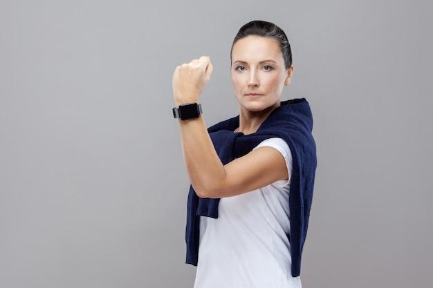 Portret van dominante brunette vrouw in casual kleding met jeans en trui op haar schouders die serieus naar camera kijkt met vuist en slim horloge. geïsoleerd, studio opname, grijze achtergrond