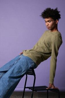 Portret van donker gevild brunette model poseren op zwarte stoel schoonheid transgender in olijf tshirt