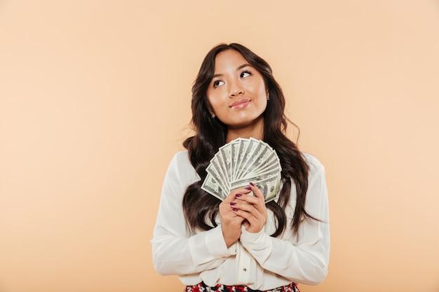 Portret van donkerbruin aziatisch wijfje dat omhoog terwijl het houden van ventilator van 100 dollarsrekeningen kijkt die succesvolle onderneemster over perzikachtergrond zijn