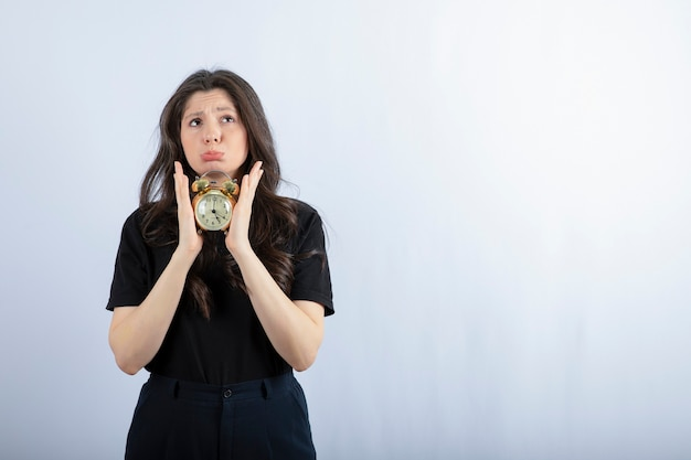 Portret van donkerbruin meisje in de zwarte klok van de uitrustingsholding op witte muur.