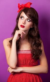 Portret van donkerbruin meisje in een rode jurk en strik op paars