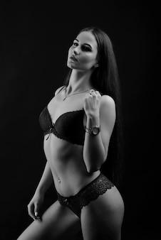 Portret van donkerbruin meisje in ondergoed dat zich in de studio met zwarte achtergrond bevindt.