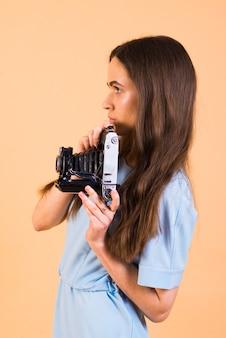 Portret van donkerbruin wijfje met een camera in hand op een gele muur. geïsoleerd.