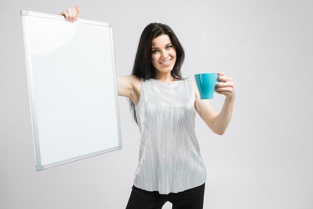 Portret van donkerbruine glimlachende vrouw die in blouse een kop en een raad houdt
