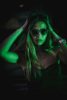 Portret van donkerbruine kaukasische vrouw die met zonnebril lichtgroene leds bekijken. nacht stadsfotografie