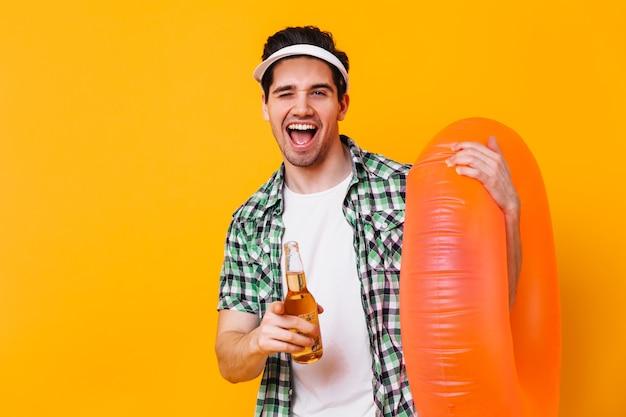 Portret van donkerbruine kerel die in witte glb naar camera richt. man met rubberen ring met bier.