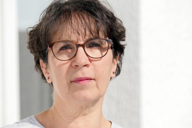 Portret van donkerbruine rijpe vrouw met glazen