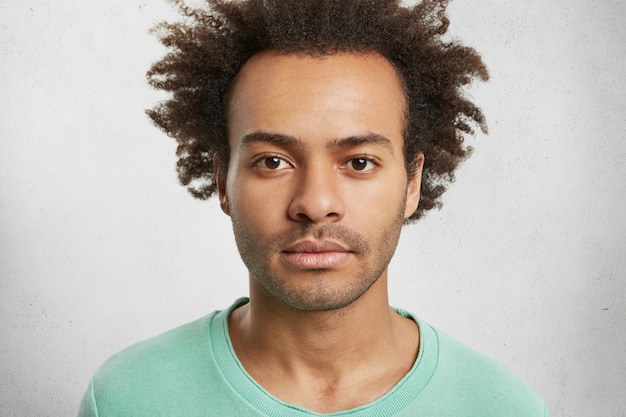 Portret van donkere huid zelfverzekerde man met krullend afro kapsel heeft rustige gezichtsuitdrukking,