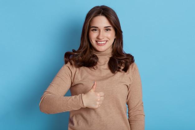 Portret van donkerharige mooie vrouwelijke student met brede glimlach, camera kijken met gelukkige uitdrukking