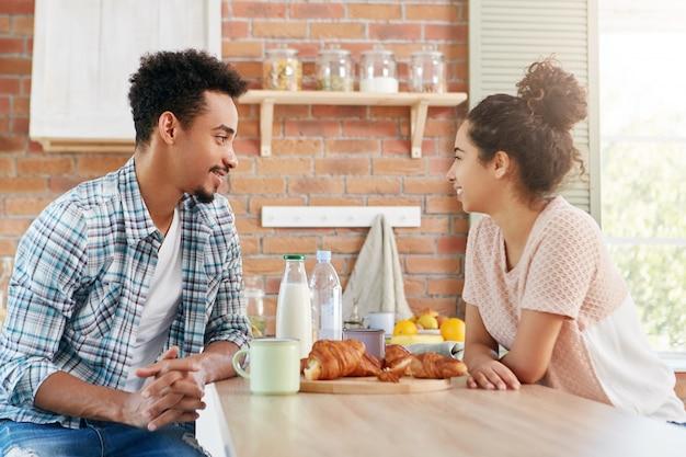 Portret van donkerhuidige gemengd ras man bezoekt zijn vriendin, heeft een aangenaam gesprek