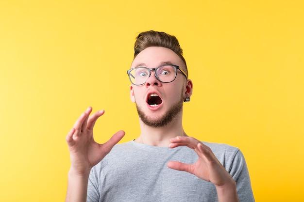 Portret van doodsbang duizendjarige man op gele achtergrond. jonge emotionele man in glazen. geschokte gezichtsuitdrukking.