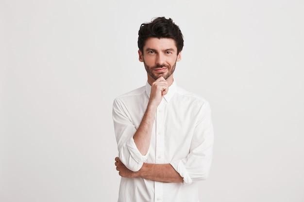 Portret van doordachte aantrekkelijke jonge zakenman met borstelhaar draagt overhemd kijkt nadenkend en zelfverzekerd geïsoleerd op wit houdt handen gevouwen