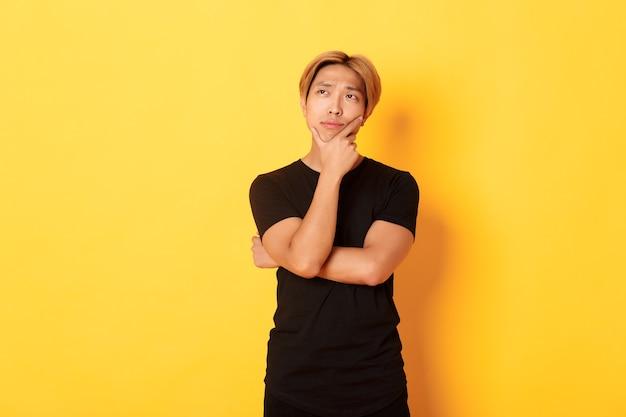 Portret van doordachte aantrekkelijke man in zwart t-shirt op zoek linkerbovenhoek. jonge man nadenkend idee, staande gele muur