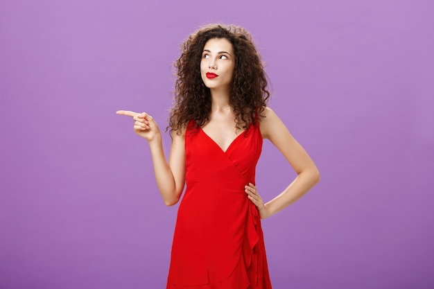 Portret van doordachte en dromerige charmante vrouw met krullend kapsel in elegante rode avondjurk p...