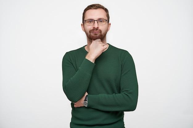 Portret van doordachte jonge brunette bebaarde man met bril en groene trui terwijl poseren, zijn kin vasthouden met opgeheven hand en lippen gevouwen houden