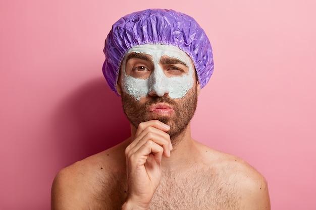 Portret van doordachte man die zijn schoonheidsroutine doet