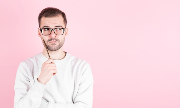Portret van doordachte man houdt potlood en kijken naar copyspace, geïsoleerd op roze achtergrond