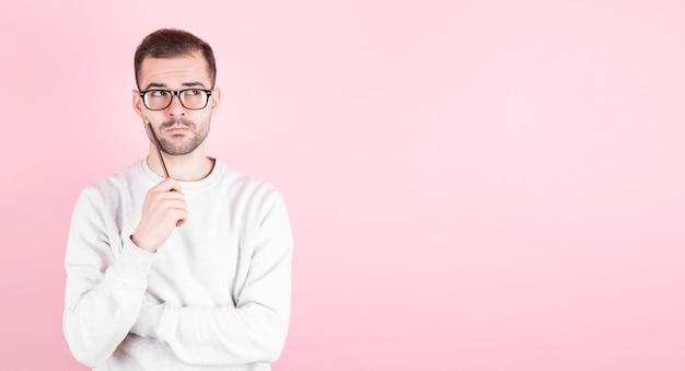 Portret van doordachte man houdt potlood en kijkt naar copyspace, over roze