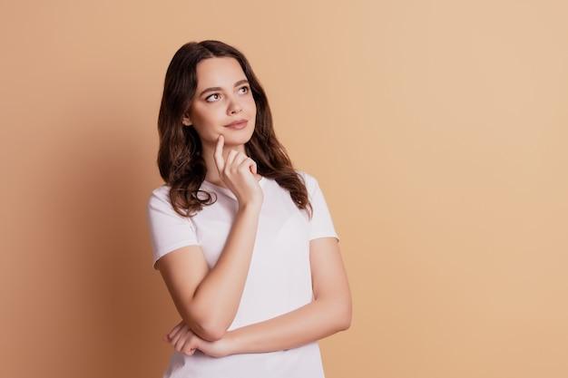 Portret van doordachte meisje vinger wang kijken lege ruimte geïsoleerd op beige achtergrond