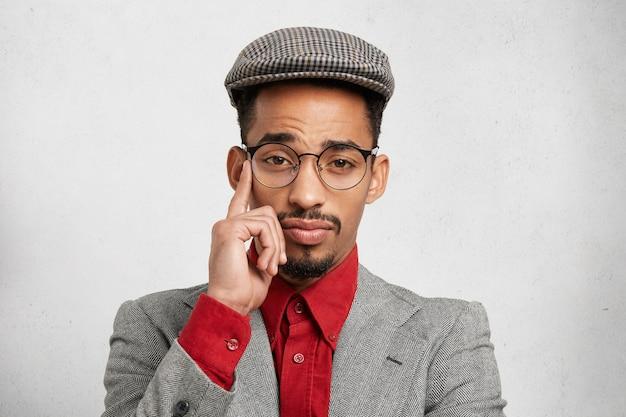 Portret van doordachte nadenkend gemengd ras mannelijke werknemer draagt trendy pet, rood shirt en jasje, heeft verstandige uitdrukking