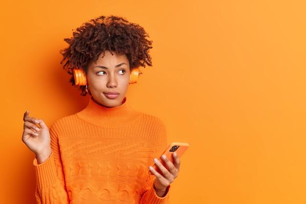 Portret van doordachte rustige vrouw met krullend haar maakt gebruik van mobiele telefoon en stereo koptelefoon geniet van favoriete afspeellijst draagt casual trui geïsoleerd over oranje muur
