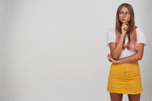 Portret van doordachte schattige jonge vrouw draagt t-shirt, gele rok en bril staat, houdt handen gevouwen en denkt geïsoleerd over witte muur