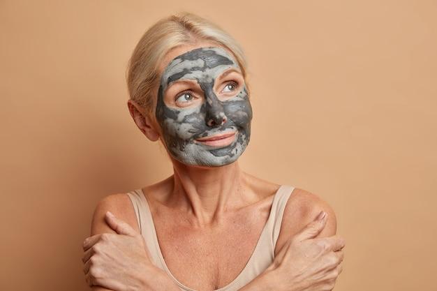 Portret van doordachte senior blanke vrouw kruist armen en raakt schouders zachtjes draagt zelfgemaakte gezichtsmasker thuis geconcentreerd weg geïsoleerd op beige muur