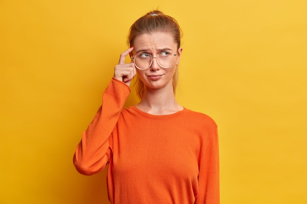 Portret van doordachte serieuze vrouw houdt de vinger op de tempel, probeert zich op iets te concentreren, draagt casual oranje trui, vormt