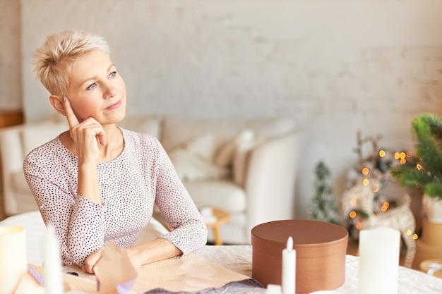 Portret van doordachte vrouw van middelbare leeftijd in elegante jurk zittend aan tafel in de kamer versierd met slinger met peinzende blik, wijsvinger op haar hoofd houden, denken hoe cadeaus voor familie in te pakken