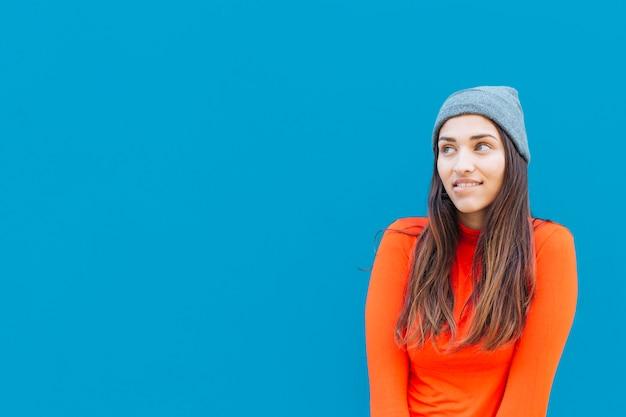 Portret van doordachte vrouw voor blauwe oppervlak