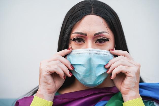 Portret van drag queen met masker en regenboog lgbt vlag - focus op gezicht
