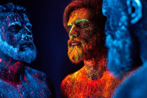 Portret van drie bebaarde mannen geschilderd in fluorescerende poeders.