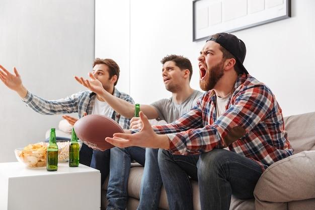 Portret van drie boos jonge mannen kijken naar amerikaans voetbal zittend thuis met bier en snacks binnenshuis