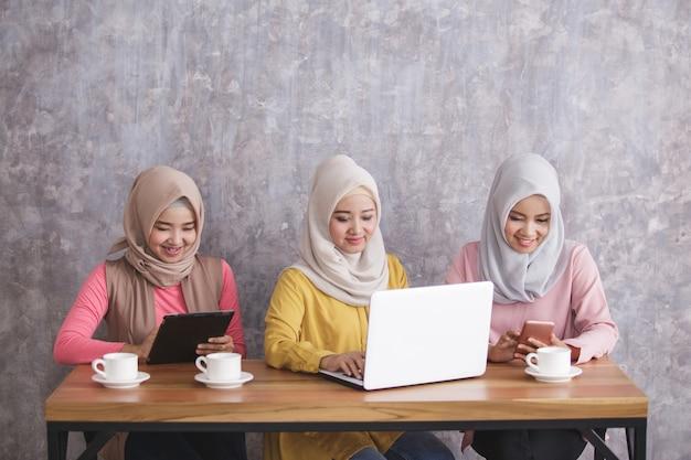Portret van drie broers en zussen met hijab zijn bezig met hun eigen gadget met betonnen muurachtergrond