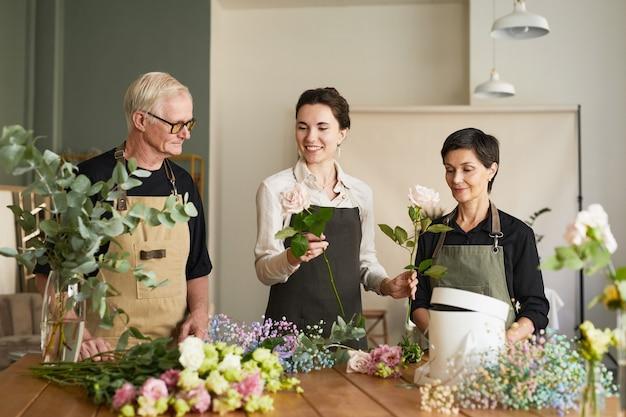 Portret van drie creatieve bloemisten die bloemcomposities voorleggen in werkplaats