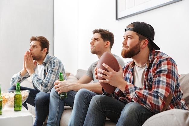 Portret van drie geconcentreerde jonge mannen kijken naar amerikaans voetbal zittend thuis met bier en snacks binnenshuis