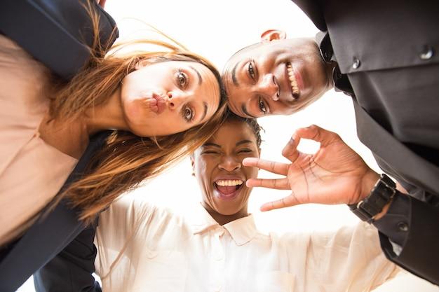 Portret van drie gelukkige collega's omarmen en grimassen