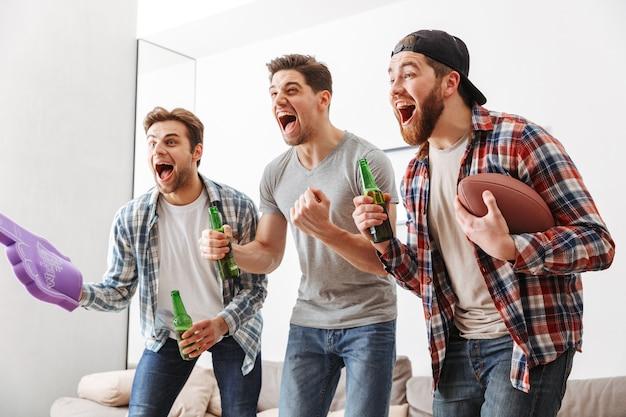 Portret van drie gelukkige jonge mannen kijken naar amerikaans voetbal thuis met bier en snacks binnenshuis