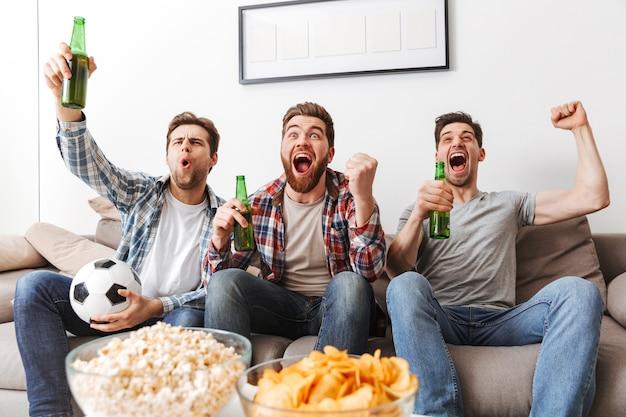 Portret van drie gelukkige jonge mannen voetbal kijken terwijl om thuis te zitten, bier drinken en snacks eten