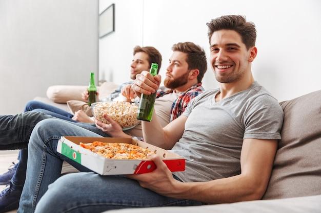 Portret van drie gelukkige jonge mannen voetbal kijken terwijl om thuis te zitten met bier en snacks binnenshuis