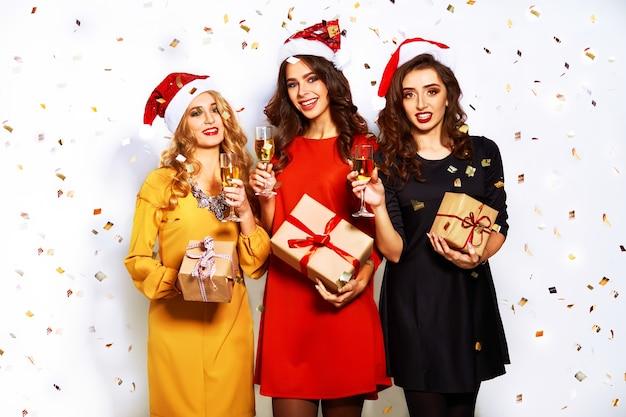 Portret van drie gelukkige jonge vrouwen in de hoed van de kerstman met gift en sterretjes.