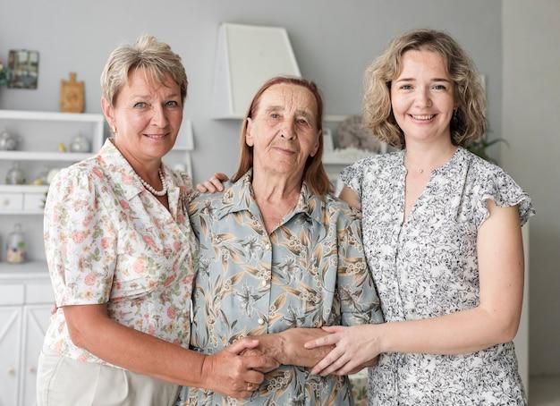 Portret van drie generatie kaukasische vrouwen die camera bekijken die zich verenigt