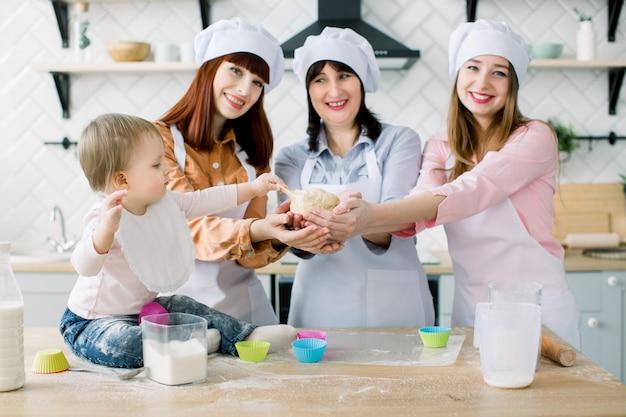 Portret van drie generaties van vrouwen die cupcakes in de keuken bakken, weinig babymeisje die met deeg spelen. gelukkige familie samen houden van harmonie kerst koken en moederdag concept